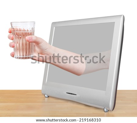 hand holding natural water in glass leans out TV screen isolated on white background - stock photo