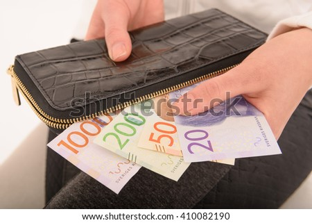 Hand holding new Swedish bank notes and wallet. NOTE: the new model. - stock photo