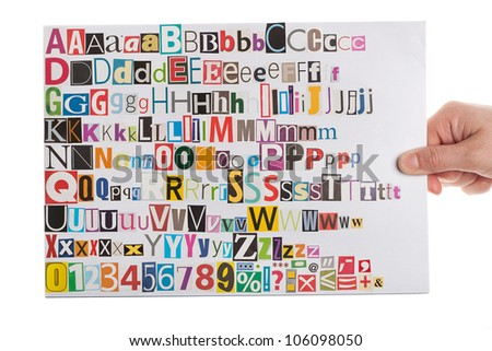 Hand holding newspaper clippings alphabet with letters, numbers and symbols, isolated on white background. - stock photo