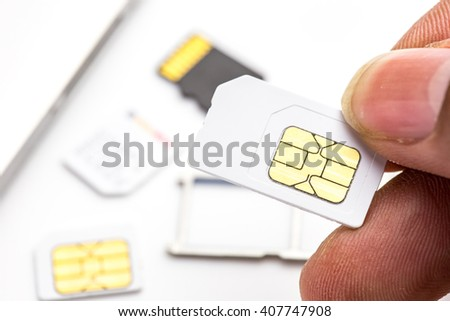Hand holding normal sim card size have sim card, tray and digital media sd card in background - stock photo