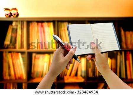 hand holding notebook and pen on blur book shelf background - stock photo