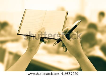 hand holding notebook and pen with blur student learning in classroom background - stock photo