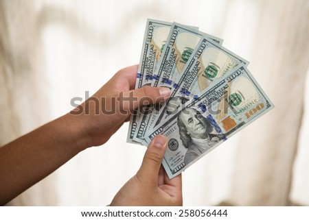 Hand holding notes of one hundred US dollars.
