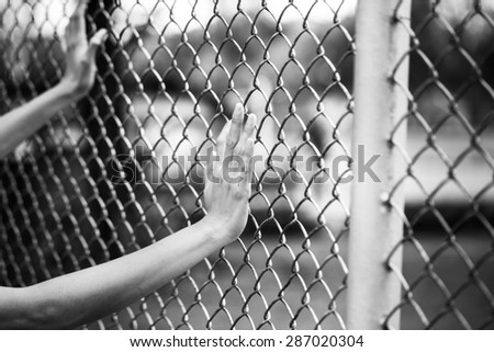 Hand holding on chain link fence, black and white concept - stock photo