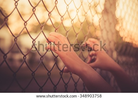 Hand holding on chain link fence , vintage - stock photo