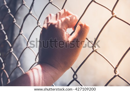 Hand holding on chain link fence, vintage tone  - stock photo