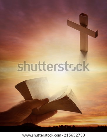 Hand holding open book, cross in sky - stock photo