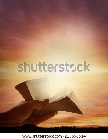 Hand holding open book in sky - stock photo