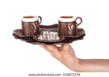 Hand holding or serving traditional Turkish coffee and  Turkish delight, isolated on white background.