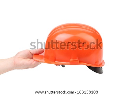 Hand holding orange hard hat. Isolated on white background. - stock photo