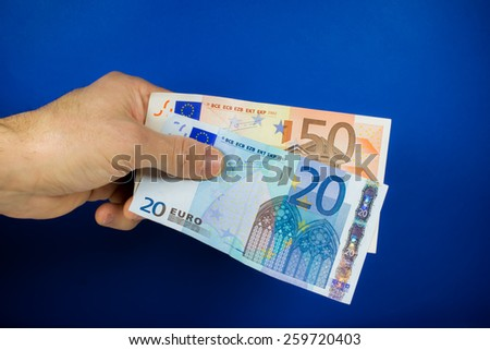 hand holding out two banknotes, on a blue background