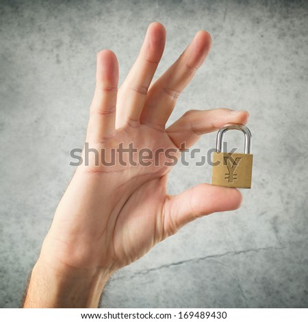Hand holding padlock with China Yuan currency symbol. Security and insurance concept. - stock photo