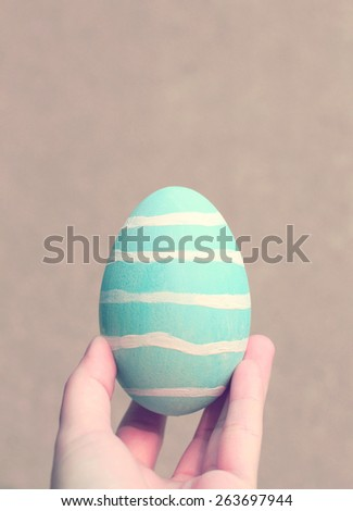Hand holding painted easter egg with retro filter effect - stock photo
