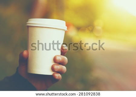 hand holding paper cup of coffee on natural morning background - stock photo