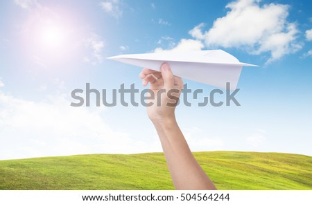 Hand holding paper plane toward cloudy blue sky. concept new innovation and creativity.