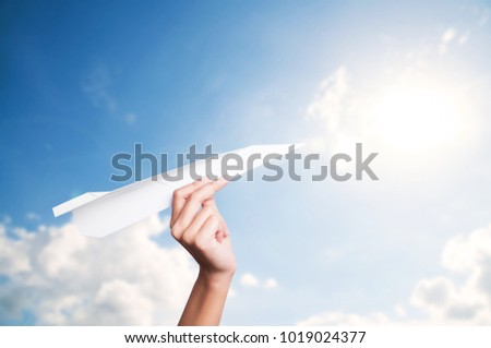 Hand holding paper plane toward cloudy blue sky concept new innovation and new creativity.