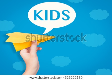 hand holding paper plane with kids text in speech bubble on blue background  - stock photo