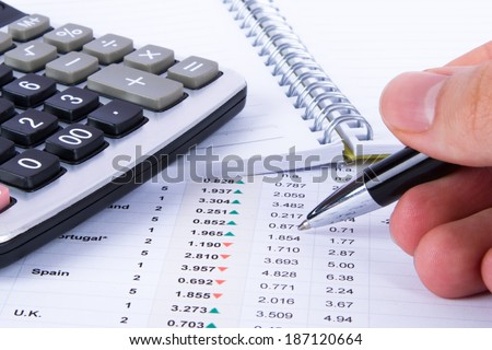 Hand holding pen and analyzing financial data for better results. - stock photo