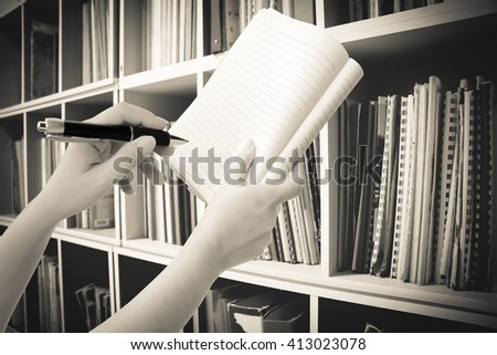 hand holding pen and notepad with blur perspective bookshelf background