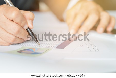 Hand holding pen for analyzing financial data and counting on document chart, business concept.