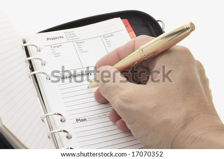 Hand holding pen writing on open organizer on white background