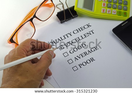 hand holding pencil check on quality check paper mark on excellent with eyeglasses calculator clip and mobile phone - stock photo