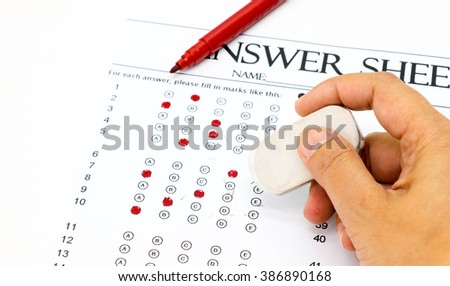 hand holding pencil eraser for erasing red marks on answer sheet represent using wrong equipment on exam