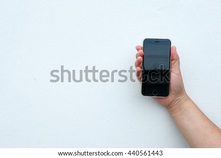 Hand holding phone with white wall background