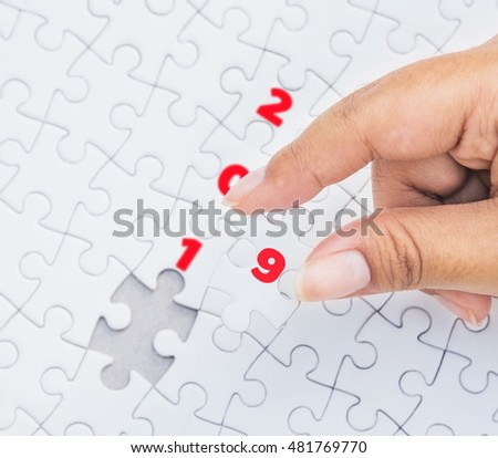 Hand holding piece of jigsaw puzzle with the last missing piece. Concept with year 2019.