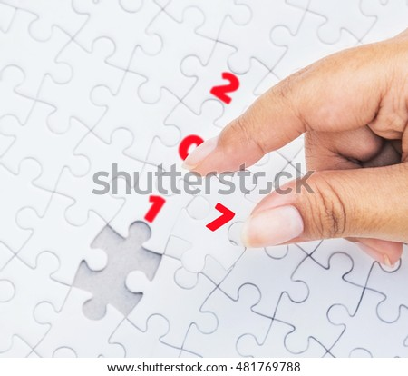 Hand holding piece of jigsaw puzzle with the last missing piece. Concept with year 2017.