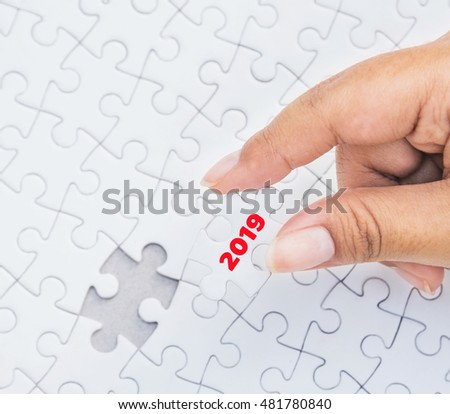 Hand holding piece of jigsaw puzzle with 2019 word piece. Concept with year 2019.