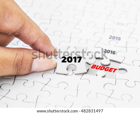 Hand holding piece of jigsaw puzzle with word 2017 to BUDGET. Concept Bussiness.