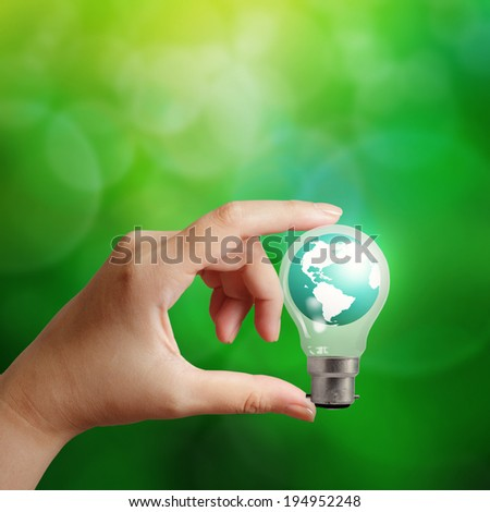 hand holding planet earth in a lightbulb as energy concept - stock photo