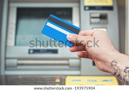 Hand holding plastic card near ATM. Bank card payment. - stock photo
