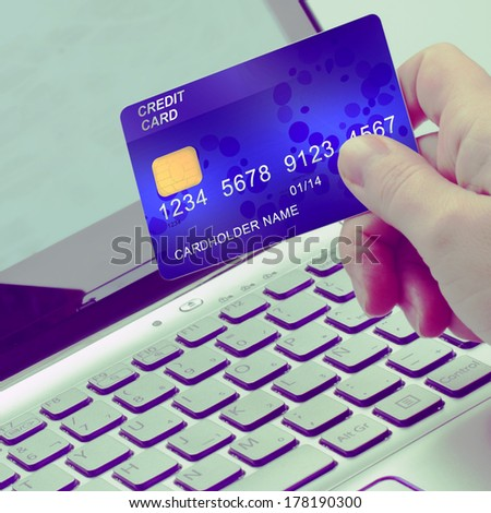 hand holding plastic card  on open notebook background - stock photo
