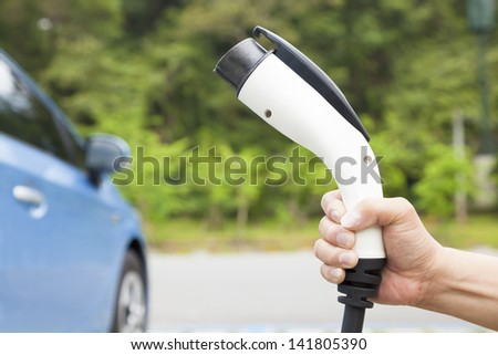 hand holding plug in connector for Charging electric car - stock photo