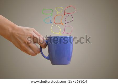 Hand holding purple mug with hand-drawn multicolored speech bubbles - stock photo