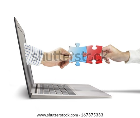 Hand holding puzzle coming out from screen to connect with another, in white background