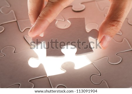 hand holding puzzle piece - stock photo
