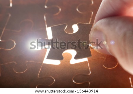 hand holding puzzle piece close up - stock photo