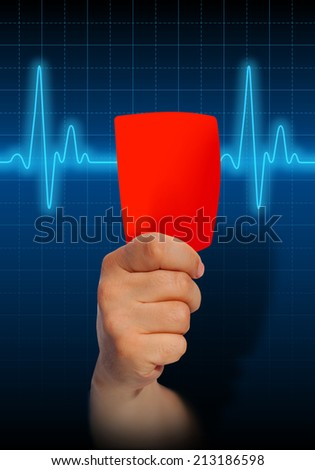 Hand holding red card on heart rate monitor expressing warning on heart condition, health hazard - stock photo