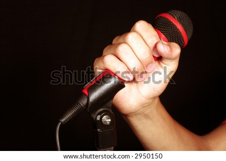 Hand holding red dynamic microphone isolated on black - stock photo