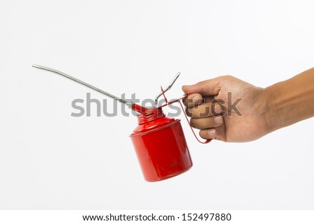 Hand holding red oil can - stock photo