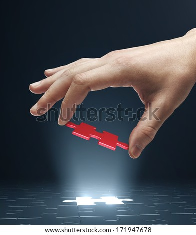 hand holding red puzzle isolated on white - stock photo