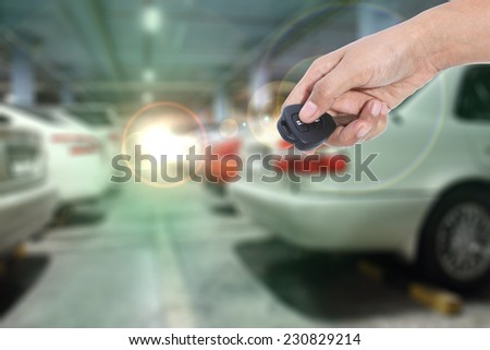 Hand holding remote control car key - stock photo