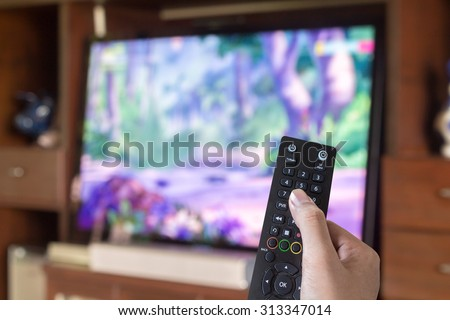 Hand holding remote control directed on the television - stock photo