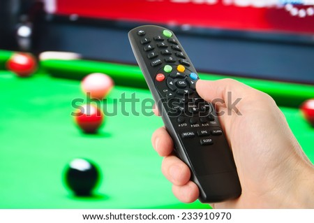 Hand holding remote control in front of tv  - stock photo