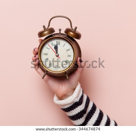 Hand holding retro alarm clock on pink background