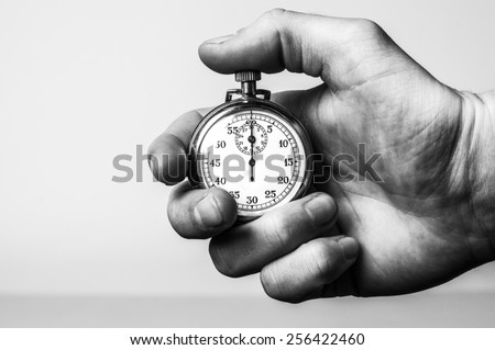 Hand holding retro stopwatch in black & white - stock photo