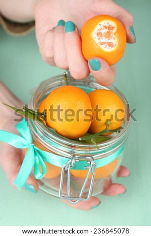 Hand holding ripe tangerine, close up - stock photo